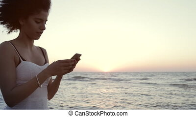 Profile of young woman walking on the beach and texting -...
