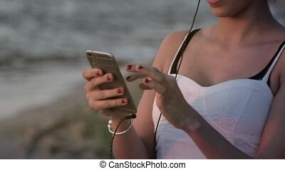 Smiling young female with smartphone on the beach - Model...