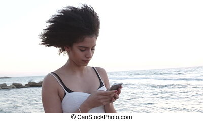 Smiling young woman reading text message on phone - Model...