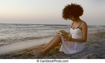 Relaxed young female sitting seaside with book - Model with...
