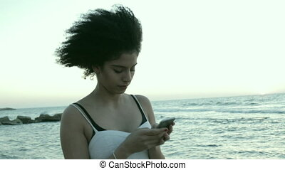 Smiling young woman texting - Model with mixed race features...