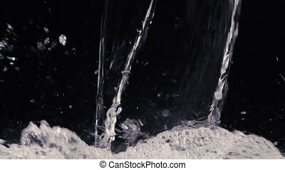 Flowing water on black background in slow motion