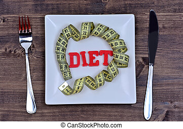Diet word with centimeter on white plate closeup