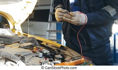 Mechanic in gloves checks electro fuse relay - electric...