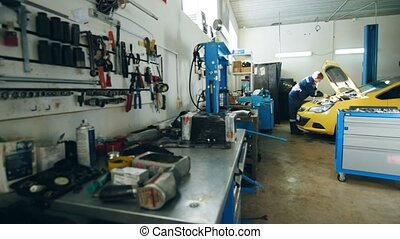 Small car garage - auto mechanic checks engine in hood of...