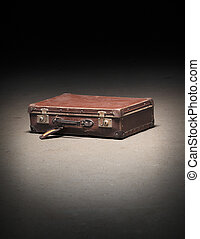 Suitcase - Old worn brown suitcase on dirty concrete floor