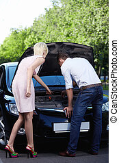 Mending - A young girl shows men how to repair cars