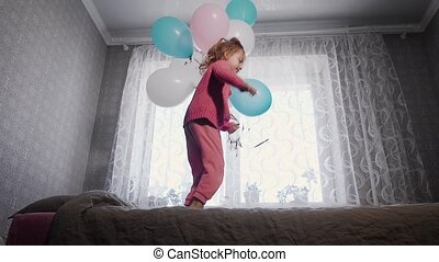 Happy little girl jumping near the window on the bed in the nursery with the bunch of air balloons in her hands and looking at the camera. Small female child is happily bouncing on the sofa.