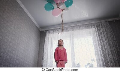 Happy little girl standing near the window on the bed in the nursery with the bunch of air balloons above. Small female child is jumping up on the sofa in the room trying to catch colourful balls.