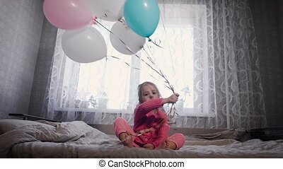 cute little girl with blond hair, dressed in pink pajamas sitting on a bed of parents, and waving from side to side balloons filled with helium. The balls of different colors - blue, white and pink