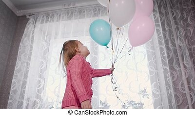 The child in the room. The baby in hands has several multi-colored balls. The girl goes on a bed, talks and is played with balloons. Balls of light colors, pink, white, blue.