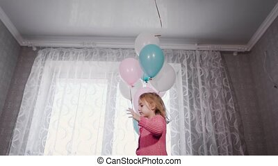 Sweet girl with blond hair standing on the bed of their parents playing with balloons filled with helium, but one white ball flew and the girl joyfully jumps up to catch it