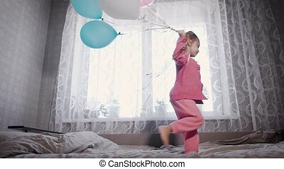Happy little girl is running near the window on the bed in...