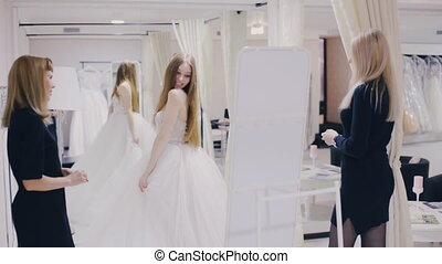 pretty girl trying on wedding gown and spinning in bridal...