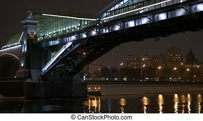 View from the deck of the ship, which floats on the River, along the waterfront decorated for the holiday. Swims under a beautiful bridge.