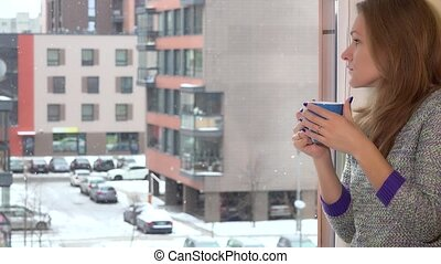 Serious woman looking through flat house window with cup of...