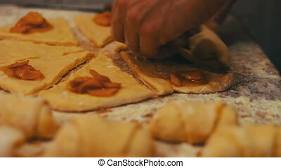 A woman puts on fresh pieces of dough apricot jam in the...