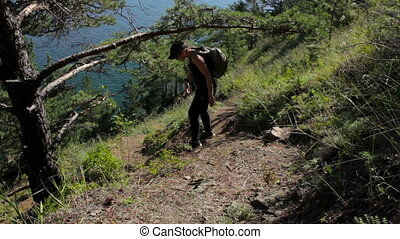 Girl coming down the steep mountainside to ocean. Young woman descend to the sea