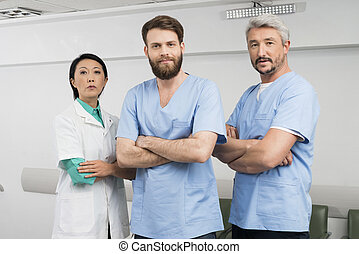Confident Doctors Standing Arms Crossed In Hospital