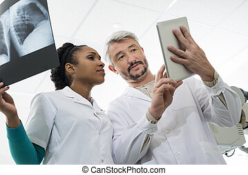 Doctors With X-ray Using Digital Tablet In Hospital