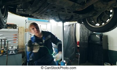 Mechanic unscrews the detail of the car's bottom in garage...