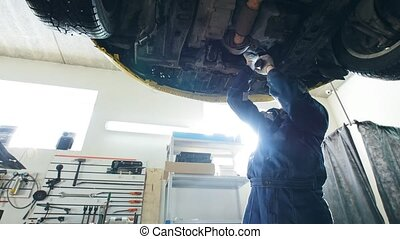Garage auto service - mechanic checks the bottom of the...