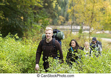 Hiker With Friends Walking Amidst Plants In Forest - Young...