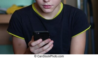 Boy teenager holds smartphone web phone online game the site...