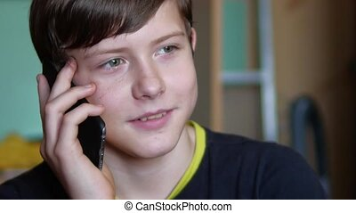 Boy teenager holds smartphone phone online game web the site...