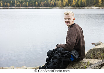 Happy Male Hiker Sitting On Lakeshore - Portrait of happy...