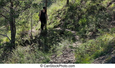 Girl climbs up the hill. A young woman goes on a forest trail in the mountains