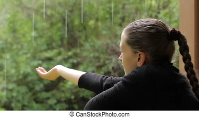 Girl sticks her hand under the rain, trying to collect the falling raindrops
