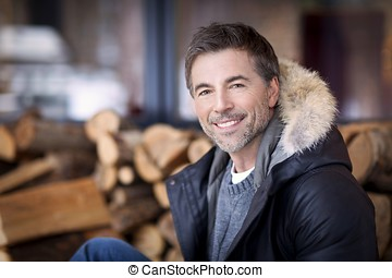 Mature man smiling at the camera. At the country house -...