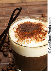 coffee with milk froth, cocoa powder and standing vanilla beans on wooden background with coffee beans