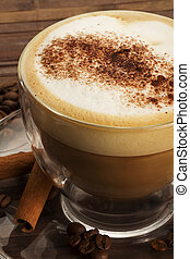 cappuccino with chocolate powder on milk froth and cinnamon sticks on wooden background