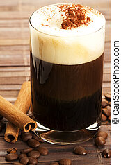 espresso in a straigt glass with milk froth cocoa powder, cinnamon sticks and coffee beans aside on wooden background
