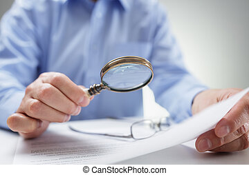 Businessman with magnifying glass reading documents -...