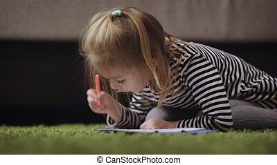 Girl with blond hair, dressed in a gray striped dress and tights is sitting on the green carpet and rasskrashivaet pictures in an album for drawing. She likes to paint markers