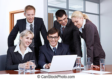 Workflow - Employees of the office looking at laptop monitor