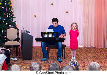 girl sings while her father plays synthesizer - girl sings...