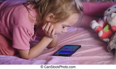 Beautiful child with blond hair, in a pink shirt lying on...