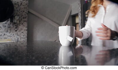 Woman takes mug with tea bag goes out from modern kitchen in...