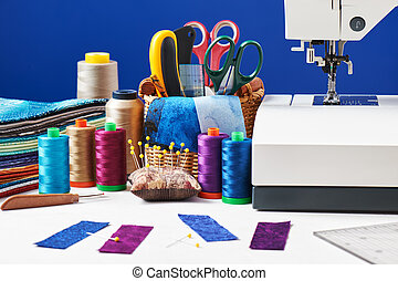 Sewing accessories in a basket and spools of threads next to...