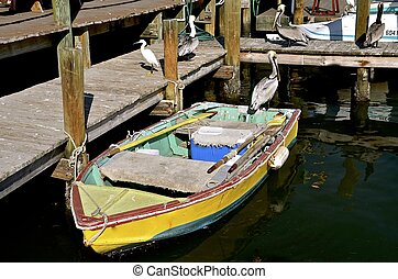 Colorful row boat and pelicans at a wharf