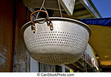 Colander hangs from a soffit - An old vintage colander hangs...