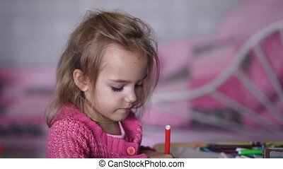 Beautiful little girl in pink cardigan drawing the...