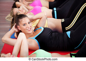 Group of people doing stretching exercise in gym