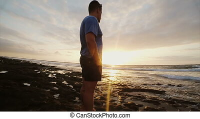 Man on the beach looking at beautiful sunset. Male watching...