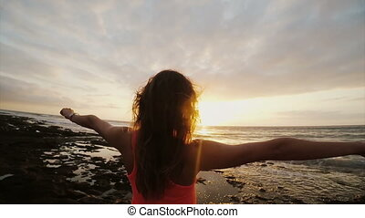 Young woman on beach looking at beautiful sunset. Female watching at horizon, wind blowing hair. Enjoying the seascape.