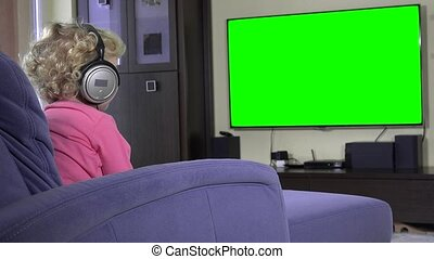 Little kid watching television with big headphones. Green...